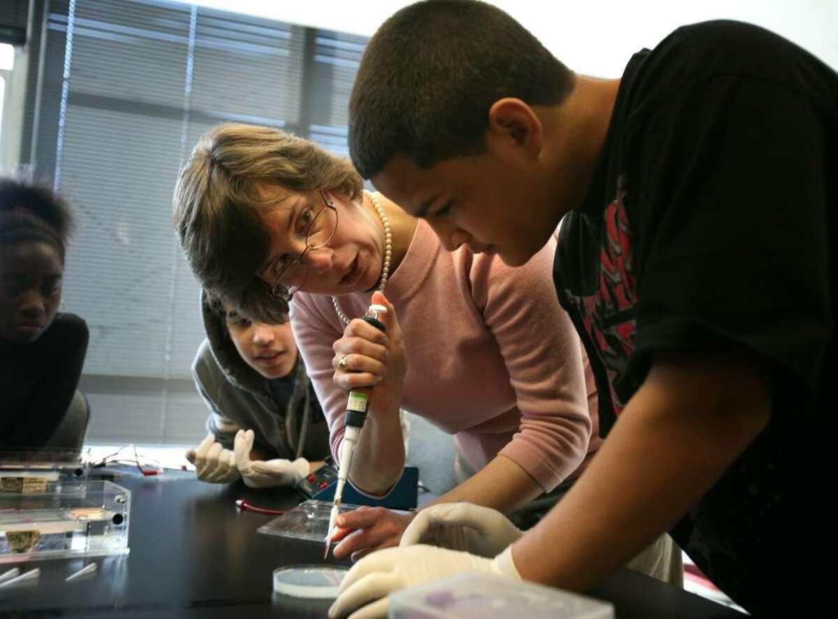 Sacred Heart University biology professor Suzanne Deschenes shows Bridgeport Central sophomore Eric Crespo how to load a sample for DNA testing.