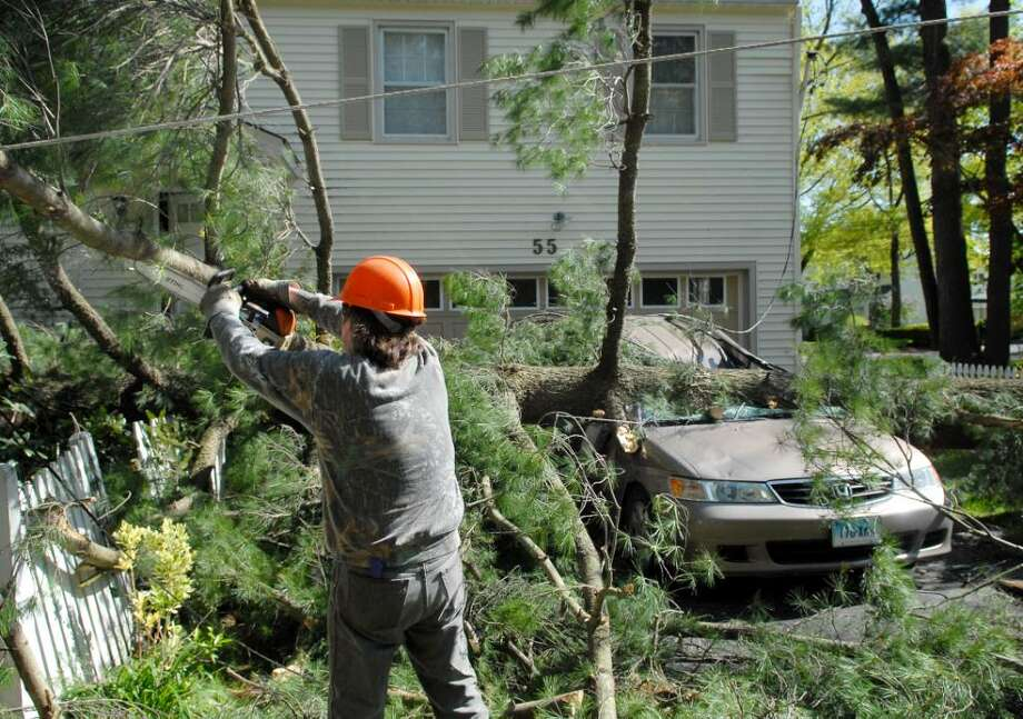 Town of Greenwich tree department worker, Joe Stempien, cuts away branches of a pine tree, which blew over onto a vehicle at 55 Harding Road in Old Greenwich during high winds, Thursday, April 29, 2010.  According to Peter Fusaro of Old Greenwich, who lives in the neighborhood, no one was injured. Photo: Bob Luckey / Greenwich Time