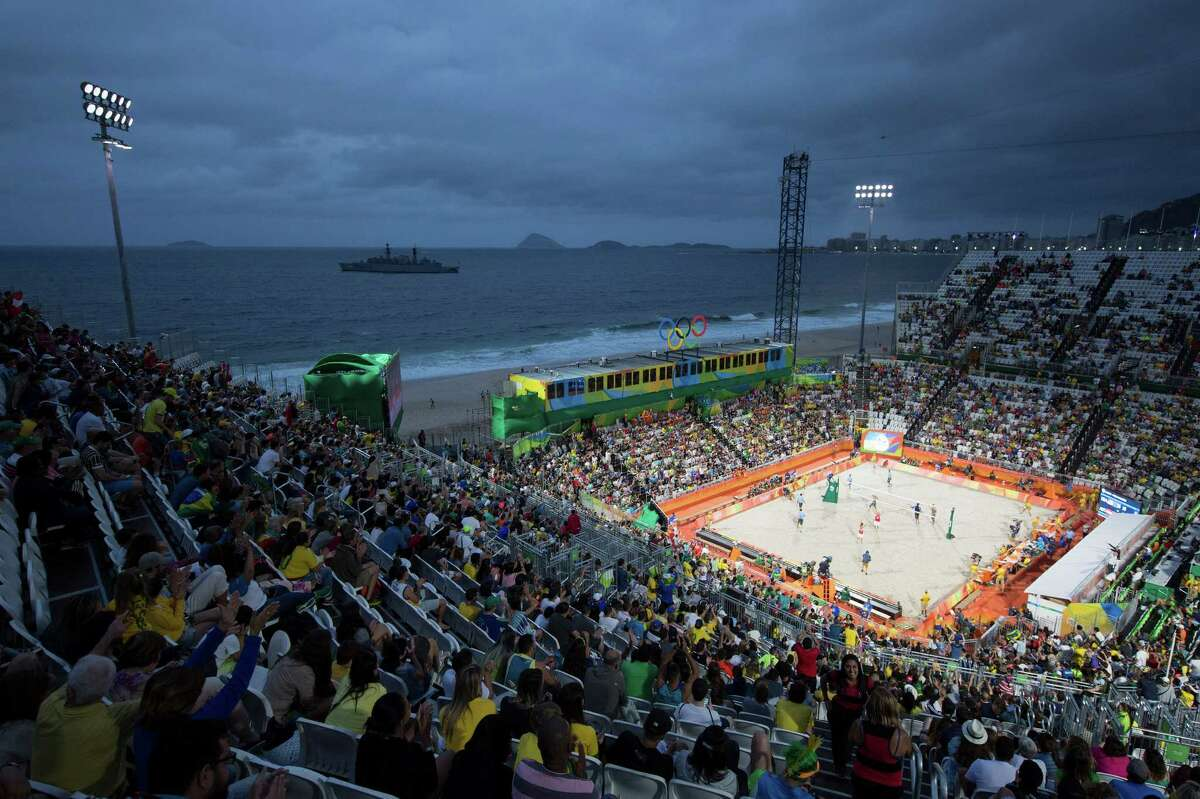 A Brazilian Navy ship patrols the bay in front of Copacabana beach during a men's beach volleyball match between Austria and United States for the 2016 Summer Olympics in Rio de Janeiro, Brazil, Monday, Aug. 8, 2016 (AP Photo/Leo Correa)