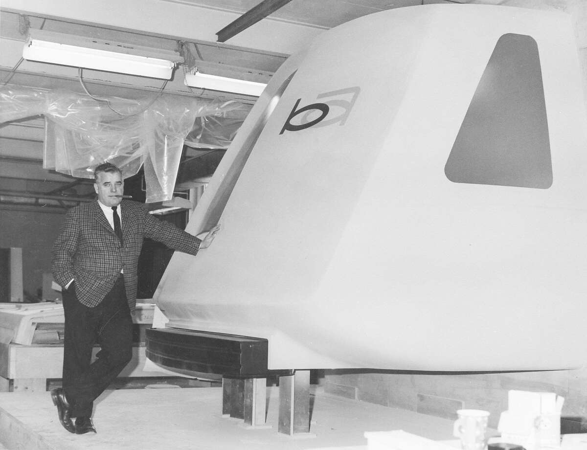 A Bay Area Rapid Transit official leans on a model BART car in 1965.