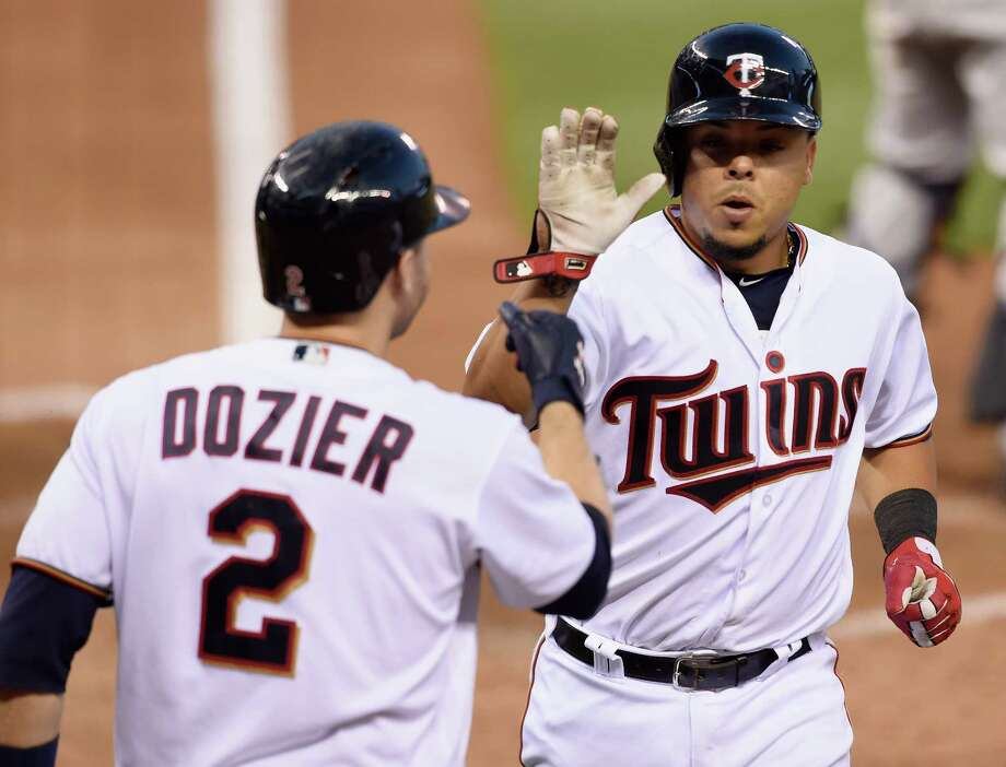 MINNEAPOLIS, MN - AUGUST 08: Brian Dozier #2 of the Minnesota Twins congratulates teammate Juan Centeno #37 on scoring a run against the Houston Astros during the fifth inning of the game on August 8, 2016 at Target Field in Minneapolis, Minnesota. The Twins defeated the Astros 3-1. Photo: Hannah Foslien, Getty Images / 2016 Getty Images