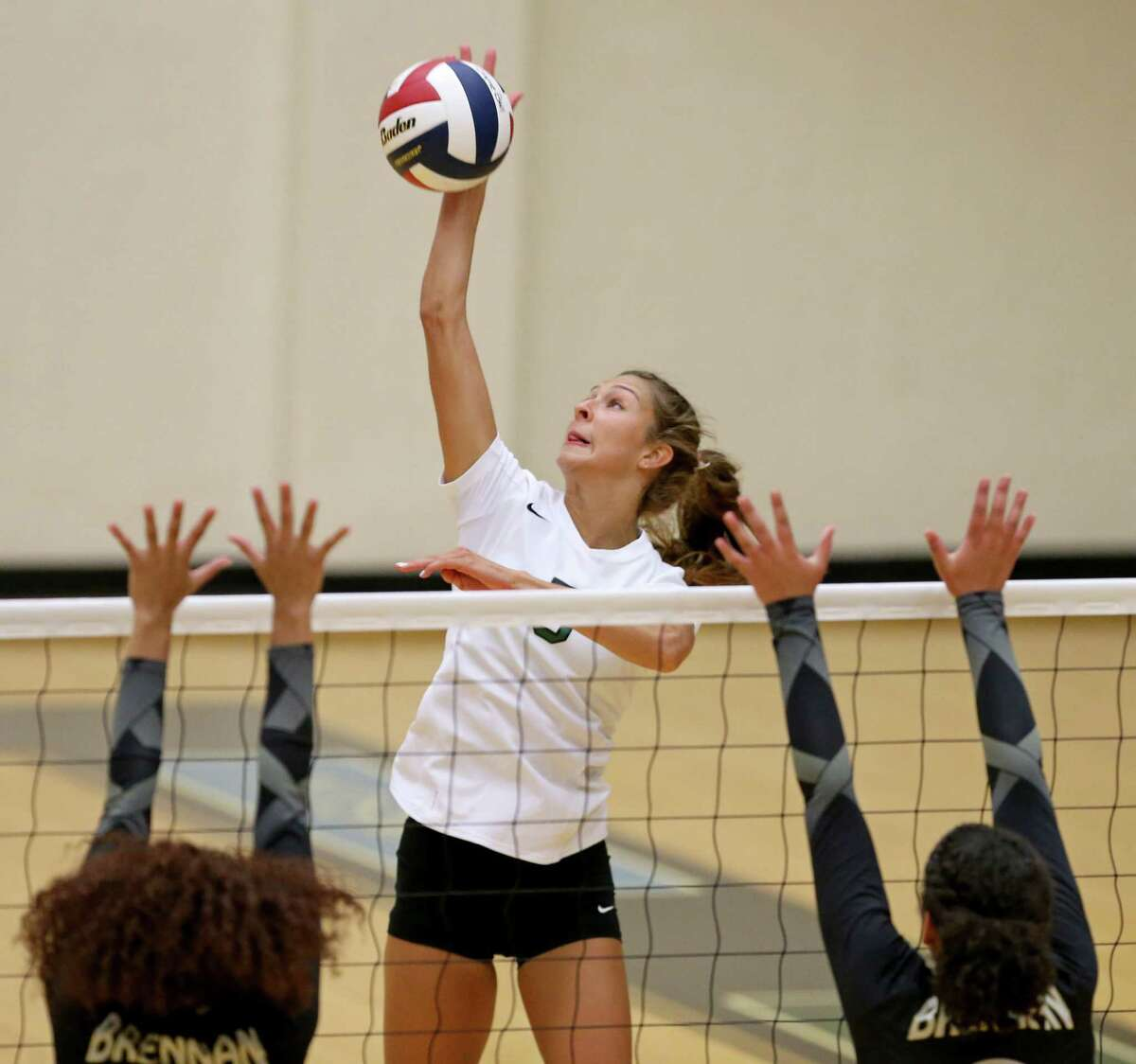 Reagan's Camryn Ennis goes up for an attack against Brennan defenders during their season opening match Monday Aug. 8, 2016 at Littleton Gym. Reagan won 25-17, 25-13, 25-22.