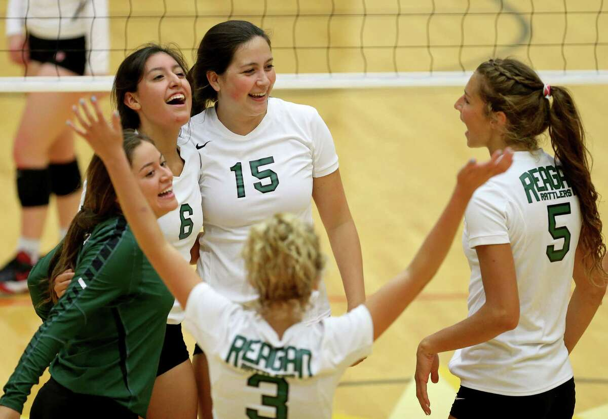 Reagan players celebrate after a point against Brennan during their season opening match Monday Aug. 8, 2016 at Littleton Gym. Reagan won 25-17, 25-13, 25-22.