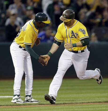 Stephen Vogt is congratulated by third base coach Ron Washington, after hitting a home run off Baltimore Orioles pitcher Kevin Gausman in the first inning. Photo: Ben Margot, Associated Press