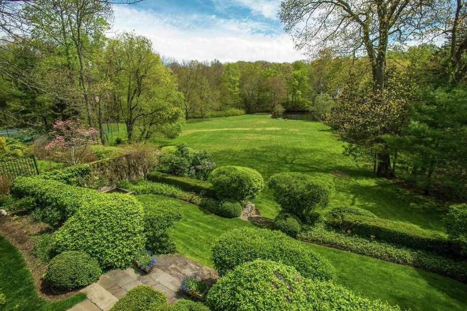 With flowering perennial gardens frames by formal boxwoods and ivy-covered stone wall, the property features lovely garden rooms tucked throughout the property. Photo: Contributed Photo / Hearst Connecticut Media / New Canaan News