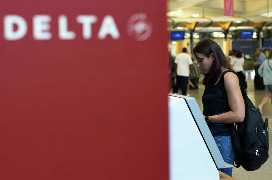 A Delta Air Lines passenger checks in Monday at Hartsfield-Jackson Atlanta International Airport. Those left stranded by Delta's outage have a few options. Photo: Branden Camp /Associated Press / FR171034 AP