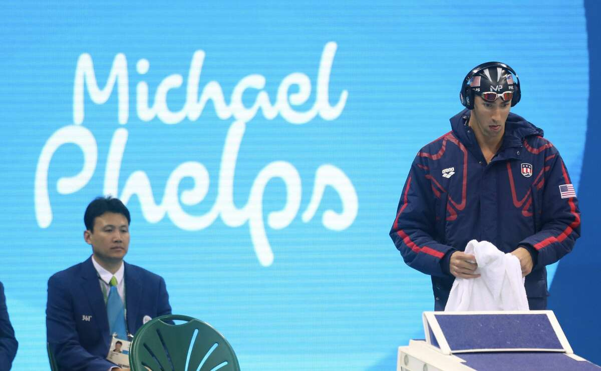 """Michael Phelps Michael Phelps is known to zone out with music - blasted out of huge headphones - ahead of a competition and has been noted to always walk to the starting block at the pool, remove his headphones and swing his arms exactly three times before a race. What's on his pre-race soundtrack? The New York Times reported that this year, Phelps listens to a mix of """"Eminem, Young Jeezy and a more recent addition, Eric Church."""""""