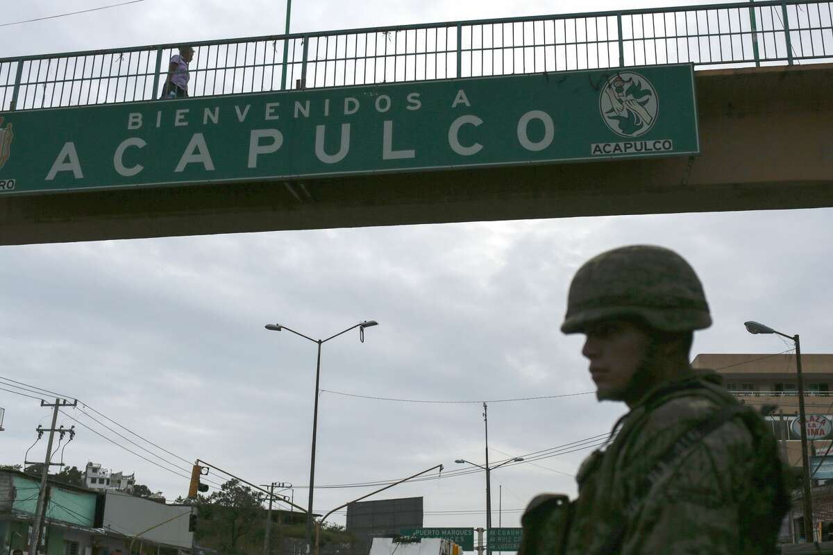 A Mexican soldier stands guard under a footbridge with an inscription that reads Welcome to Acapulco in Acapulco, Mexico on July 14, 2016. With a population of 810,000 the touristic resort of Acapulco ranks as one of the most violent cities in the world, with a crime rate of 111 murders per 100,000 inhabitants in 2015.