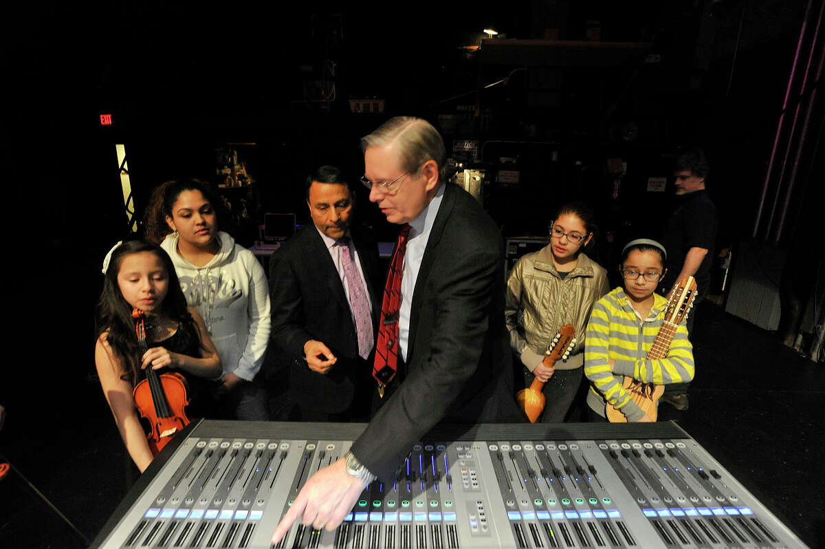 Harman Chairman, President and CEO Dinesh Paliwal shows Mayor David Martin a digital mixing board as they are flanked by INTAKE music students during the INTAKE organization's education session with people from audio equipment manufacturer Harman at the Palace Theatre in Stamford, Conn., on Monday, March 16, 2015.
