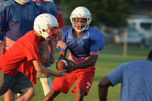 Tomball junior quarterback Tybo Taylor works a handoff to sophomore running back Ryan Herrera last week.