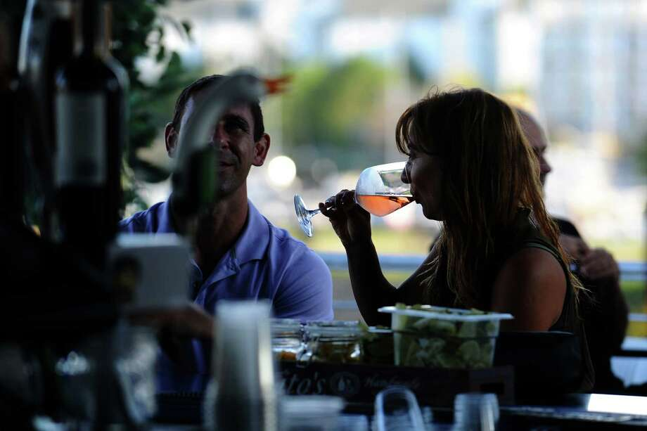 CC Cirulli, of Stamford, enjoys a glass of wine on the rooftop bar at Sign of the Whale in Harbor Point on Monday evening, August 8, 2016. Photo: Michael Cummo / Hearst Connecticut Media / Stamford Advocate