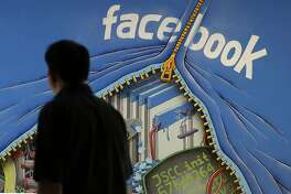 """FILE - In this June 11, 2014, file photo, a man walks past a mural in an office on the Facebook campus in Menlo Park, Calif. Facebook is taking an aggressive new tack that blocks ad blockers on the desktop version of its service, insisting that well-made, relevant ads can be """"useful."""" At the same time, the world's biggest social media company says it is giving users easier ways to decide what types of ads they want to see. Unless, of course, the answer is """"none."""" (AP Photo/Jeff Chiu, File)"""