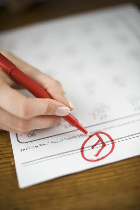 Teacher writing F grade on worksheet Photo: Tetra Images/Getty Images/Tetra Images RF