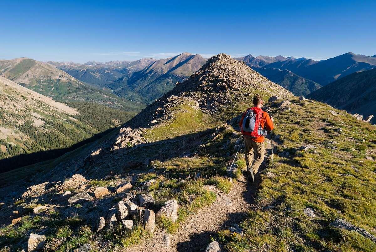 Man recreating and exploring along mountain ridge high in mountains. �LaPlata Peak, Sawatch Range, Colorado. �Captured as a 14-bit Raw file. Edited in 16-bit ProPhoto RGB color space.