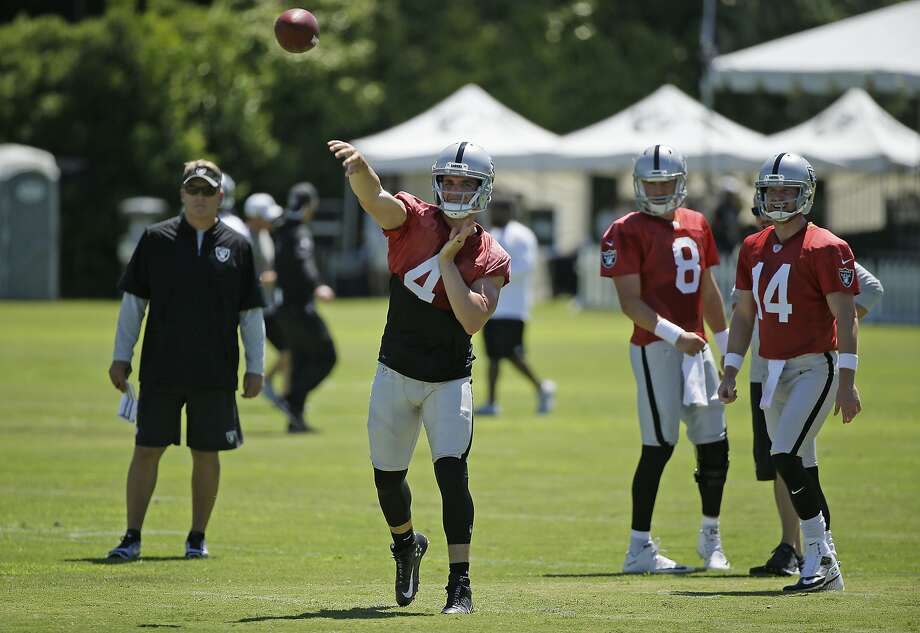 Oakland Raiders quarterback Derek Carr throws during practice as head coach Jack Del Rio, left, and quarterbacks Connor Cook (8) and Matt McGloin (14) look on. Photo: Eric Risberg, Associated Press