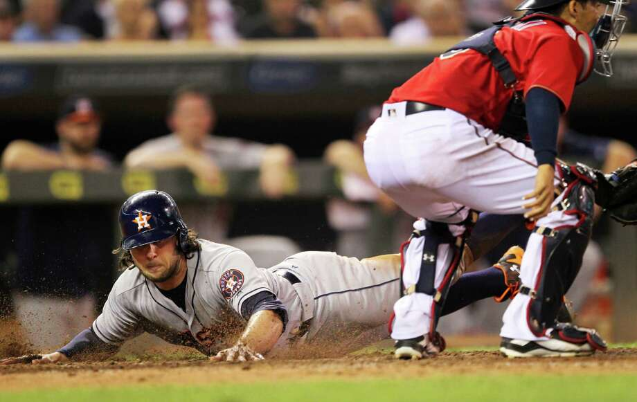 Houston Astros center fielder Jake Marisnick slides past Minnesota Twins catcher Kurt Suzuki to score on a sacrifice fly in the ninth inning during a baseball game on Tuesday, Aug., 9, 2016 in Minneapolis. The Astros defeated the Twins 7-5.(AP Photo/Andy Clayton-King) Photo: Andy Clayton-King, Associated Press / FR51399 AP