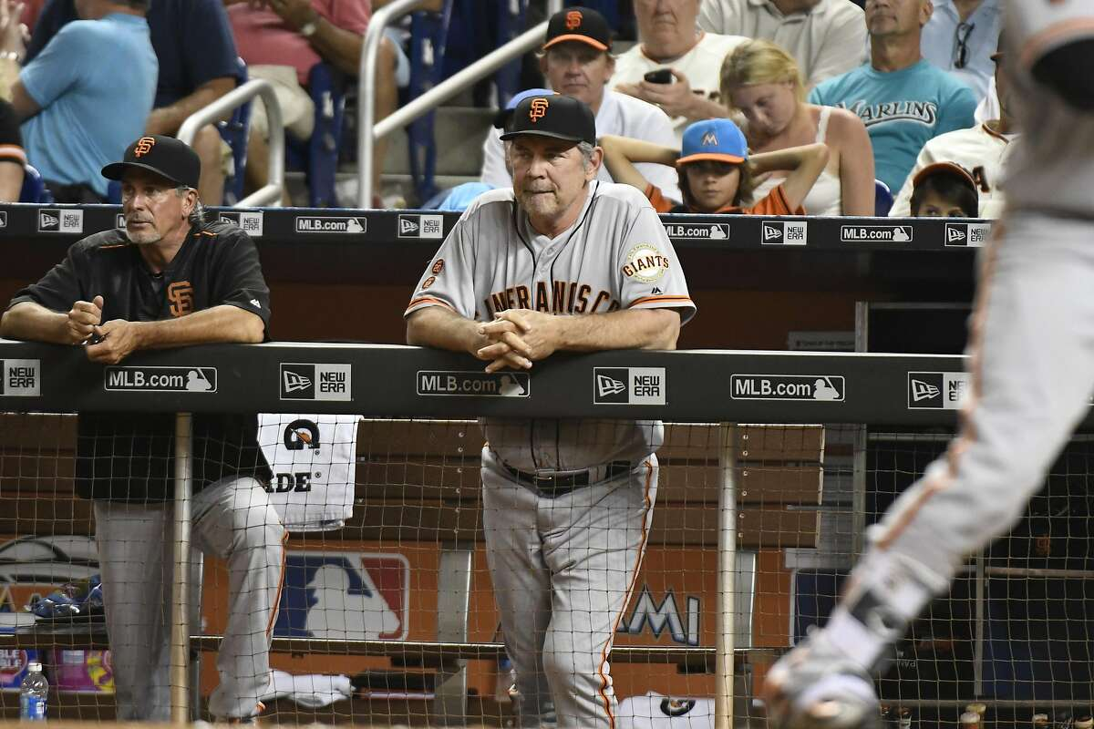 Bruce Bochy watches from the dugout during the game against the Miami Marlins at Marlins Park.