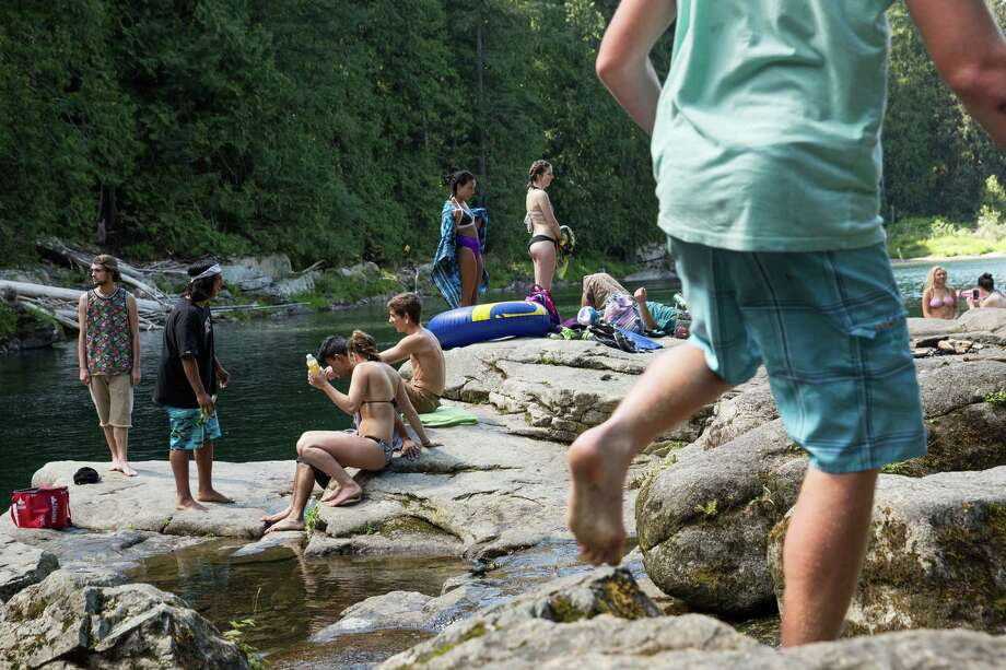 Groups of friends enjoy one another's company at the swimming hole at Eagle Falls just off of U.S. Highway 2 in Snohomish County. Eagle Falls sits just 60 miles from Seattle on the Skykomish River but offers a getaway from the hustle of the city. Photo: GRANT HINDSLEY, SEATTLEPI.COM / SEATTLEPI.COM