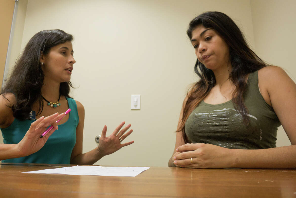 Financial Coach Paola Castro, left, and client Olga Lovera go over materials for a financial counseling class at Memorial Assistance Ministries. Financial Coach Paola Castro, left, and client Olga Lovera go over materials for a financial counseling class at Memorial Assistance Ministries.