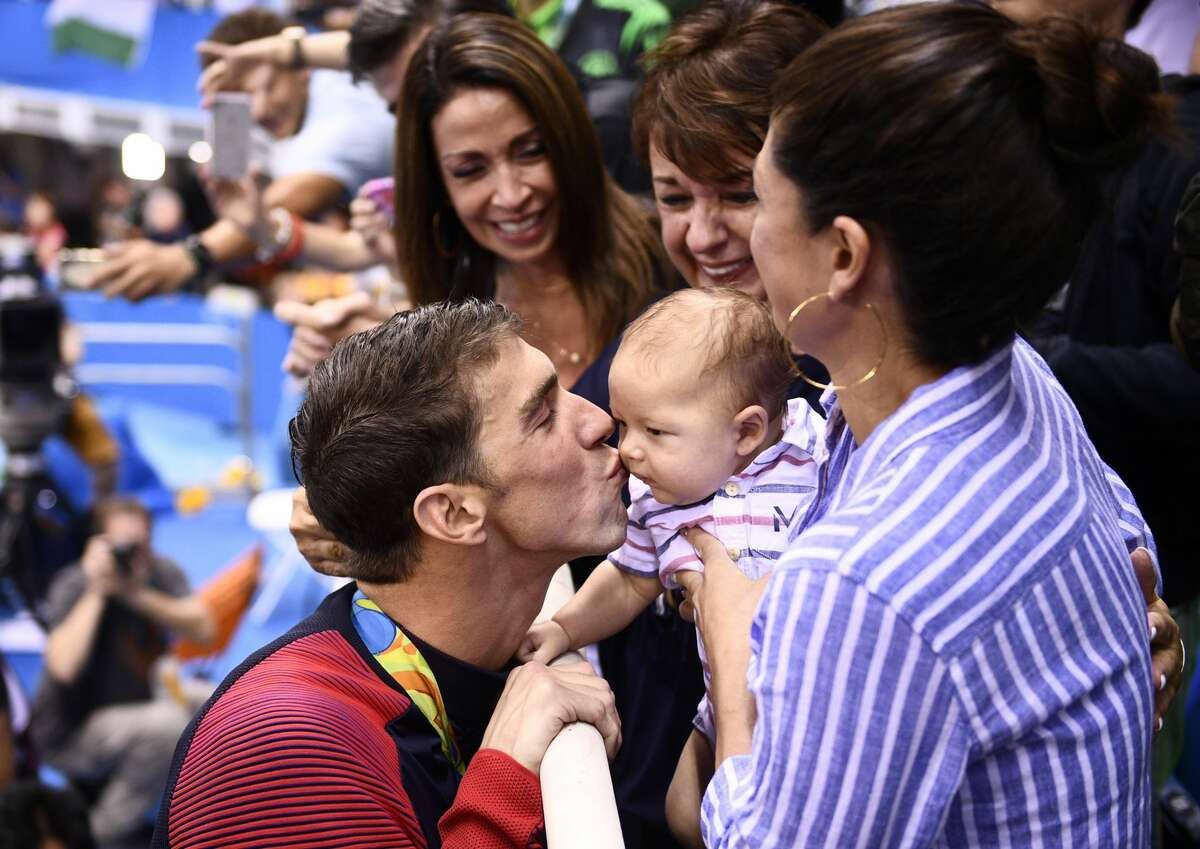 Athlete: Michael Phelps County: United States of America Event: 200m Butterfly Final Michael Phelps kisses his son Boomer next to his finacee Nicole Johnson and mother Deborah after he won the Men's 200m Butterfly Final during the swimming event at the Rio 2016 Olympic Games at the Olympic Aquatics Stadium in Rio de Janeiro on August 9, 2016.