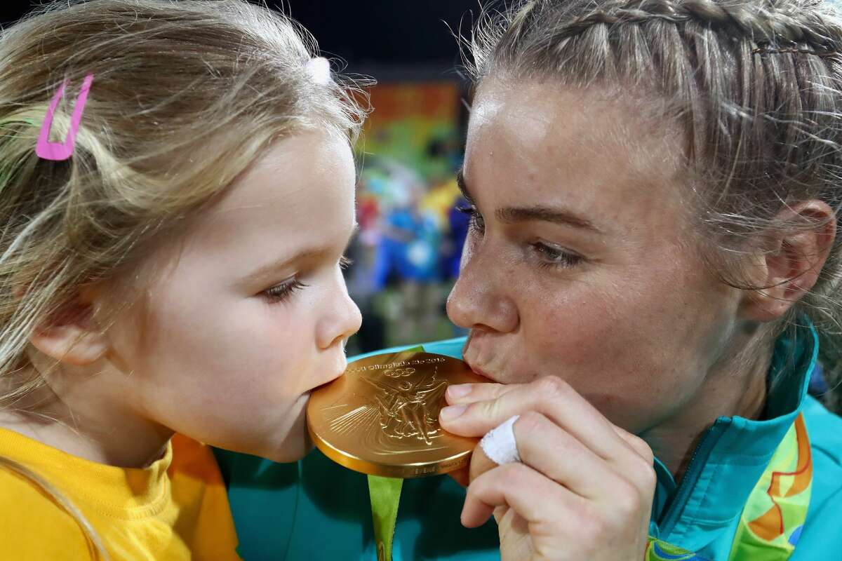 Athlete: Nicole Beck County: Australia Event: Rugby Nicole Beck of Australia kisses her Gold medal with her daughter Sophie Beck after the medal ceremony for the Women's Rugby Sevens on Day 3 of the Rio 2016 Olympic Games at the Deodoro Stadium on August 8, 2016 in Rio de Janeiro, Brazil.