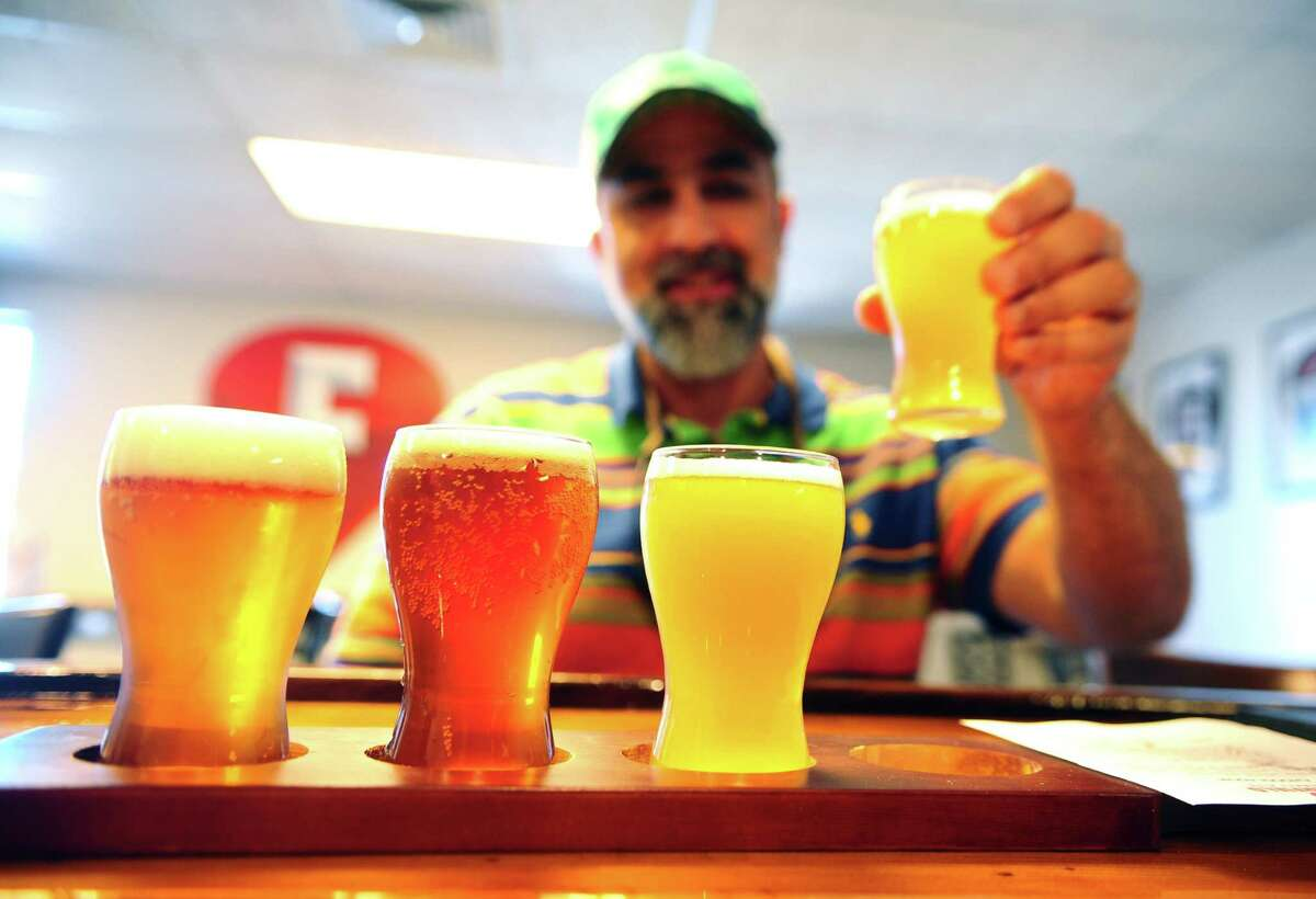 Customer Harry Yamalis, of Berlin, tries a sampler set at Fairfield Craft Ales on Honeyspot Road in Stratford, Conn., on Thursday Aug. 4, 2016. The micro brewery, which opened on July 9th, has created a line of music inspired beers like Quadrophenia Belgian Quad, Live & Let Rye and Revolution IPA.