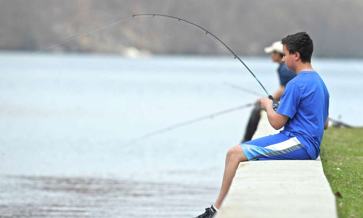 Andrew Valente, 15, of Danbury fishes from a wall in Candlewood Park on Friday, April 22, 2016, in Danbury, Conn.