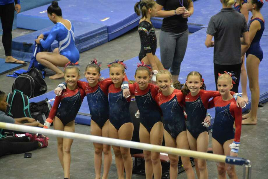 Darien Level 5 gymnasts Nadia Borja, Sofia DeStefano, Melina Cardini, Isabella DeStefano, Saskia Chermayeff, Megan Mitchell and Lucy Collins are all smiles before competing on bars at the 2016 YMCA National Championships. Photo: Contributed Photo / Darien News