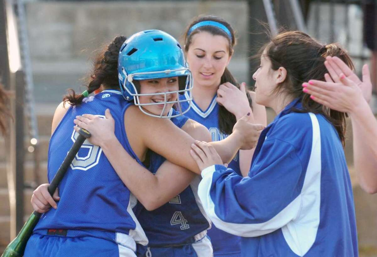 Fairfield's Elise Perazzini, facing, gets a hug from Samantha Spano after scoring and giving Ludlowe the lead as Stamford High hosts Fairfield Ludlowe in a girls softball game Thursday afternoon, April 29, 2010. Fairfield won 2-1.