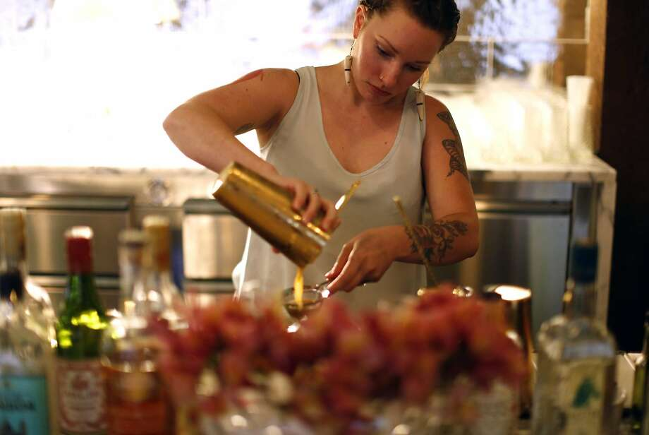Caitlin Midkiff makes a drink at Louie's Gen-Gen Room in S.F. Photo: Scott Strazzante, The Chronicle