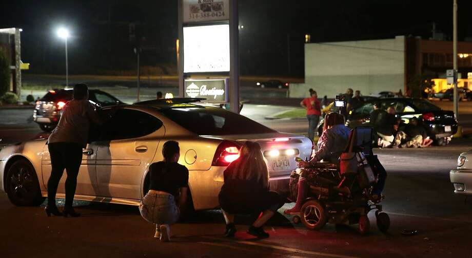 People duck behind a car after gunfire rings out during a protest Tuesday marking Michael Brown's death in Ferguson, Mo. Photo: Robert Cohen, Associated Press