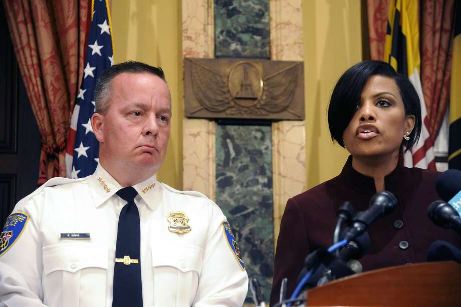 Police Commissioner Kevin Davis, left, listens as Baltimore Mayor Stephanie Rawlings-Blake speaks during a news conference at City Hall in response to a Justice Department report, Wednesday, Aug. 10, 2016 in Baltimore. The Justice Department and Baltimore police agreed to negotiate court-enforceable reforms after a scathing federal report released Wednesday criticized officers for using excessive force and routinely discriminating against blacks. (Kim Hairston/The Baltimore Sun via AP) Photo: Kim Hairston, Associated Press