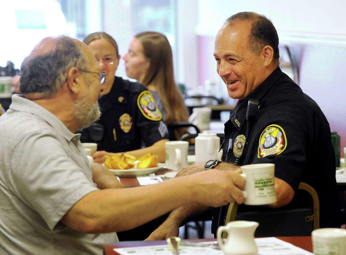 """Bethel Selectman Richard Straiton, left, chats with Bethel Officer Vinnie Lajoie, right, and Sgt. Heather Burnes, center, Wednesday morning, August 10, 2016, at Jacqueline's Restaurant on Greenwood Ave. The Bethel police held what they called """"Coffee with a Cop,"""" inviting members of the community to get to know them"""