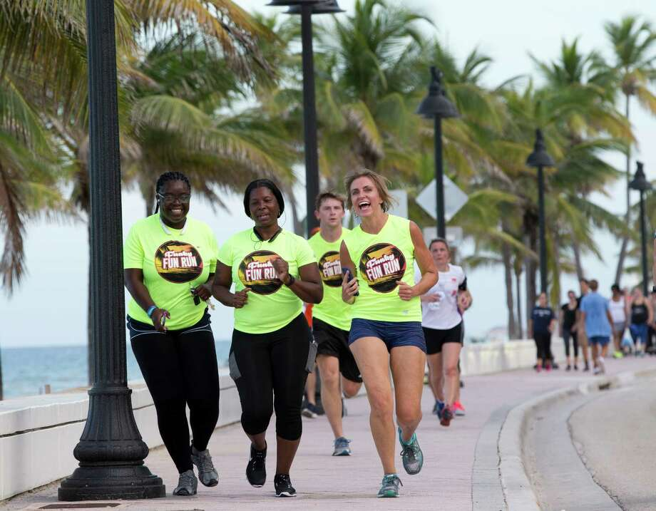 """Runners with the Westin Fort Lauderdale Beach Resort's weekly run club run toward the hotel in Fort Lauderdale, Fla. For years, business networking has centered around food and alcohol. Now it's all about grabbing your running shoes or unrolling your yoga mat and bonding over a fitness class thanks to """"sweatworking."""" Photo: Wilfredo Lee /Associated Press / Copyright 2016 The Associated Press. All rights reserved. This material may not be published, broadcast, rewritten or redistribu"""