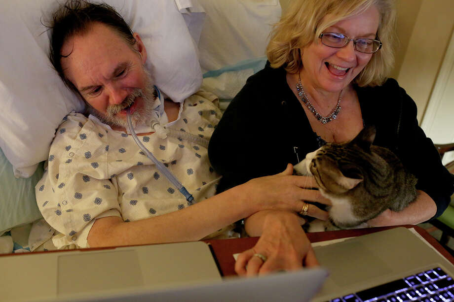 One night in late May, when Walt wouldn't open his eyes, Debra took him on a photographic tour of their lives, as their cat, Hope, nestled on her lap. He eventually opened his eyes and joined his wife on a walk down memory lane -- almost four decades bursting with experiences. Photo: Lisa Krantz / SAN ANTONIO EXPRESS-NEWS