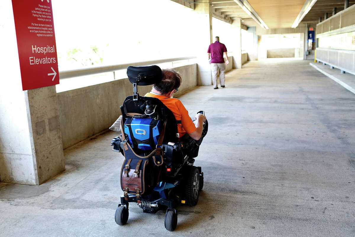 Dr. Walter Root rolls in his motorized wheelchair toward the emergency room at University Hospital after his wife, Debra found blood when she suctioned his tracheostomy tube at their home April 8. Root was admitted to the intensive-care unit, where he was treated for pneumonia. He would be transferred to other medical facilities after that as he struggled with fatal effects of Lou Gehrig's disease.