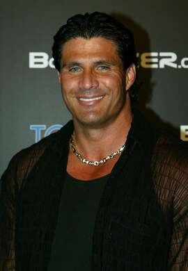 Retired baseball player Jose Canseco smiles in Beverly Hills, Calif, Friday, Oct. 8, 2004. Canseco is back in baseball, having agreed to a contract with the independent San Diego Surf Dawgs. He's planning to be their designated hitter and pitch. (AP Photo/Danny Moloshok,file)