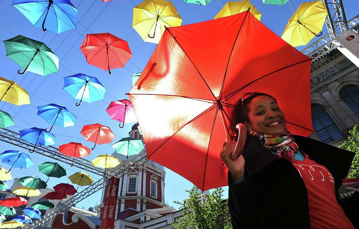 A woman carries an umbrella as she walks along 'The alley of flying umbrellas' art installation in central St. Petersburg on May 15, 2015.