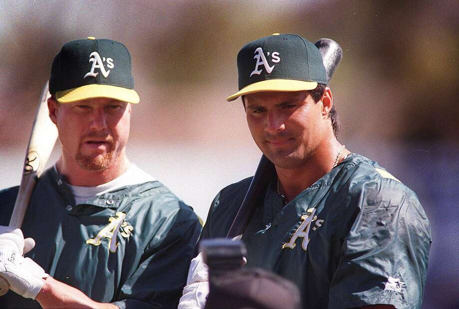 "In this file photo Mark McGwire (left) and Jose Canseco are seen reunited as the ""Bash Brothers"" after Canseco returned to the team via a trade with the Red Sox. Chronicle photo by Tim Kao"