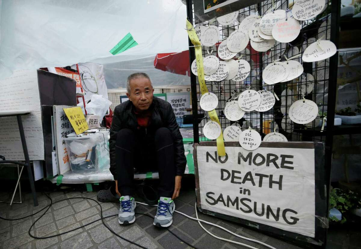 In this April 22, 2016 photo, Hwang Sang-gi, father of Hwang Yu-mi, a former Samsung factory worker who died of leukemia at the age of 22, wears shoes in order to an interview outside Samsung buildings in Seoul, South Korea. Yu-mi went to work bathing silicon wafers in chemicals at a Samsung factory that makes computer chips for laptops and other devices. Four years later, she died of leukemia. Sang-gi launched a movement demanding the government investigate health risks at Samsung Electronics Co. factories after learning another worker at the same semiconductor line of Yu-mi also had died of leukemia. (AP Photo/Ahn Young-joon) ORG XMIT: TKTT401