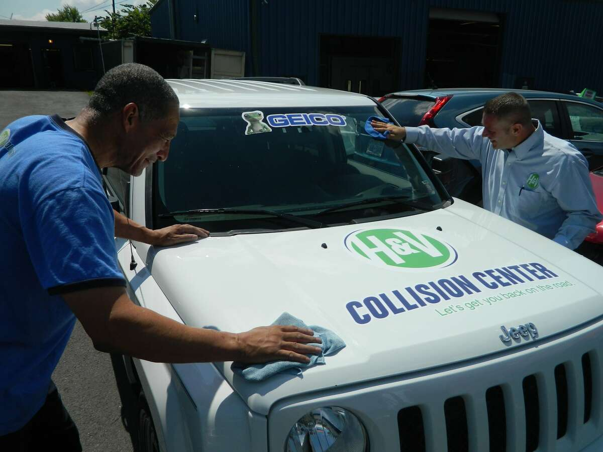 Repair technicians at H&V Collision Center put the finishing touches on one of three refurbished vehicles that will be donated to local veterans on Saturday. (H&V Collision Center)