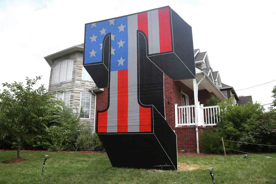 "A giant ""T"" is displayed on Sam Pirozzolo's lawn in the borough of Staten Island in New York, Wednesday, Aug. 10, 2016. Days after the torching of a giant ""T"" tribute to Donald Trump on a New York City lawn, a new, even bigger red-white-and-blue letter has risen on the same grass spot. (AP Photo/Seth Wenig) ORG XMIT: NYSW102 Photo: Seth Wenig / Copyright 2016 The Associated Press. All rights reserved. This m"