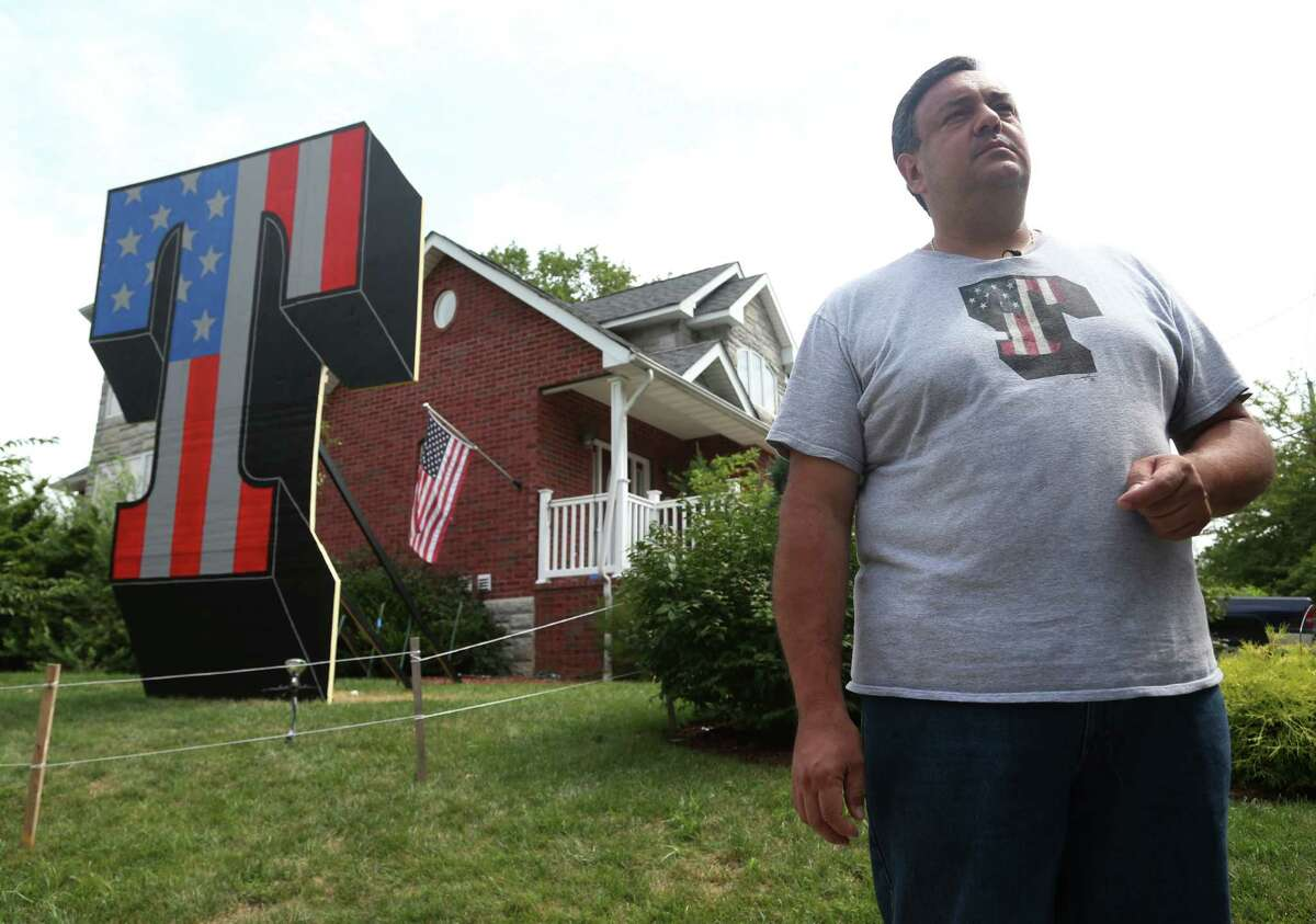 Sam Pirozzolo talks to a reporter in front of his house where a giant