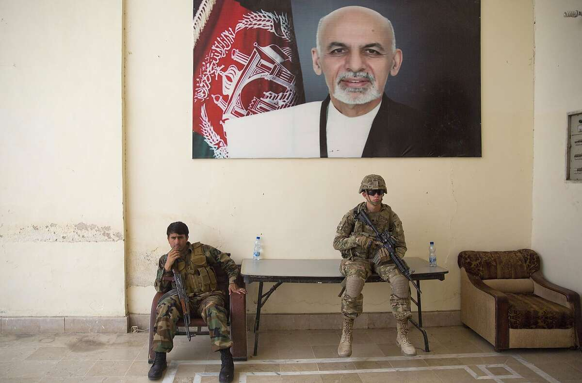FILE - In this Thursday, Aug. 4, 2016 file photo, an Afghan soldier, left, and a U.S. soldier guard during a visit of Kabul's officials, in the governor's compound in Kandahar, Afghanistan. Kareem Atal, head of the provincial council, said Wednesday, Aug. 10, 2016, that troops are being deployed to a key southern city in Helmand province where fighting is raging with the Taliban to ensure it does not fall to the insurgents. Helmand is a strategically important province for both the Kabul government and the Taliban, whose insurgency is now in its 15th year. (AP Photos/Massoud Hossaini, File)