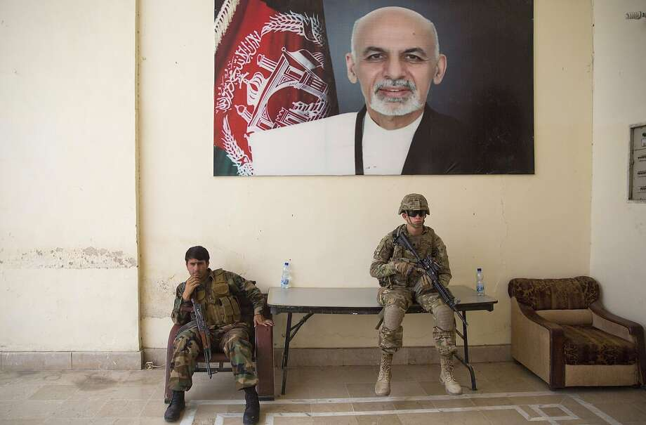 An Afghan soldier (left) and a U.S. soldier serve as guards at the governor's compound in Kandahar, Afghanistan, during an official visit by officials from Kabul. Photo: Massoud Hossaini, Associated Press