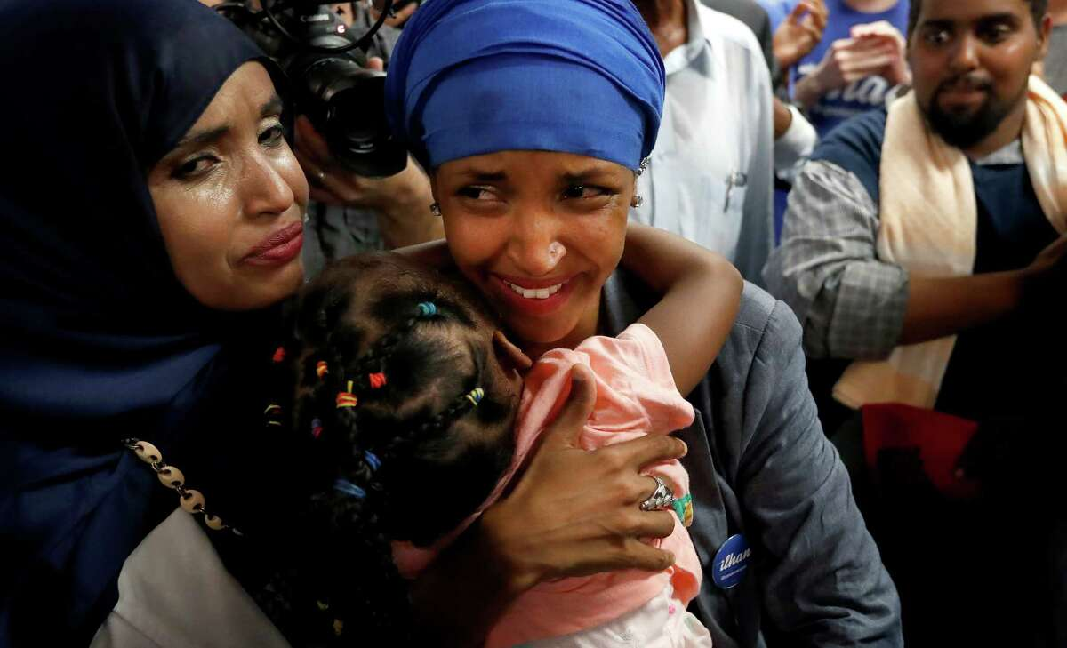 Somali activist Ilhan Omar, center, is greeted by supporters at Kalsan Tuesday, Aug. 9, 2016, in Minneapolis. Omar defeated 22-term Rep. Phyllis Kahn in Tuesday's nominating contest in the heavily Democratic Minneapolis district. (Carlos Gonzalez/Star Tribune via AP) ORG XMIT: MNMIT107