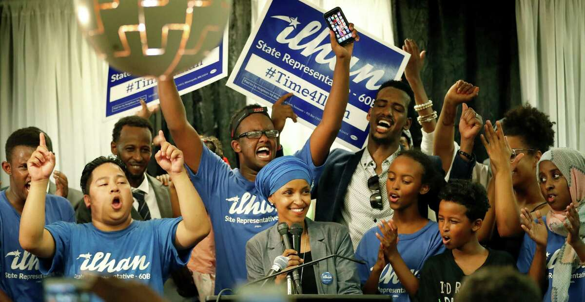 Somali activist Ilhan Omar, center, speaks to supporters at Kalsan Tuesday, Aug. 9, 2016, in Minneapolis. Omar defeated 22-term Rep. Phyllis Kahn in Tuesday's nominating contest in the heavily Democratic Minneapolis district. (Carlos Gonzalez/Star Tribune via AP) ORG XMIT: MNMIT104
