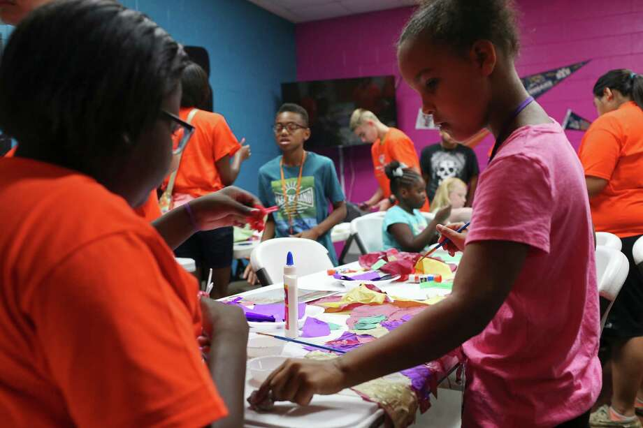 Eastside Dreamers Academy mentor Kourtney Reed, 15, left, helps out Alanah Bauman, 8, during an art project at the Eastside Boys and Girls Clubs, Tuesday, August 9, 2016. The academy is part of the OneMillionDreams program. The program helps teens, between the ages of 13 to 17 years, set goals, instill self-confidence and engage in their communities. The children were working on making paper wings for a video project. Photo: JERRY LARA, Staff / San Antonio Express-News / © 2016 San Antonio Express-News