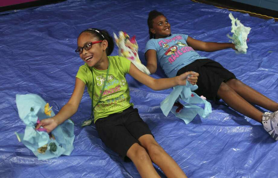 Juliann Olguin, 10, left, and Lazareah Johnson, 9, fly around in their wing as part of an art project at the Eastside Boys and Girls Clubs, Tuesday, August 9, 2016. The club runs afterschool programs that enrich children's lives and educate them. Photo: JERRY LARA /San Antonio Express-News / © 2016 San Antonio Express-News