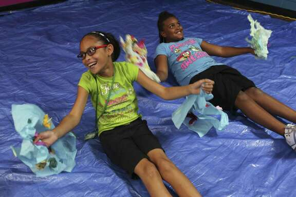 Juliann Olguin, 10, left, and Lazareah Johnson, 9, fly around in their wing as part of an art project at the Eastside Boys and Girls Clubs, Tuesday, August 9, 2016. The club runs afterschool programs that enrich children's lives and educate them.